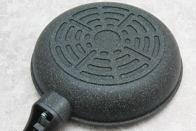 Đáy chảo phủ đá hoa cương dễ vệ sinh, được thiết kế hoa văn vòng tạo độ ma sát giữa chảo và bếp.