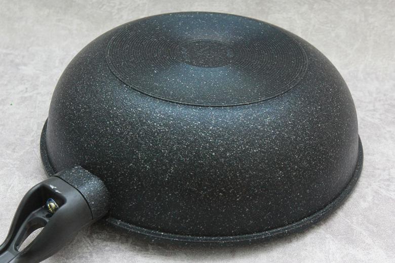 Đáy chảo phủ đá hoa cương dễ vệ sinh, được thiết kế hoa văn vòng tròn giúp chảo đứng vững được trên bếp.